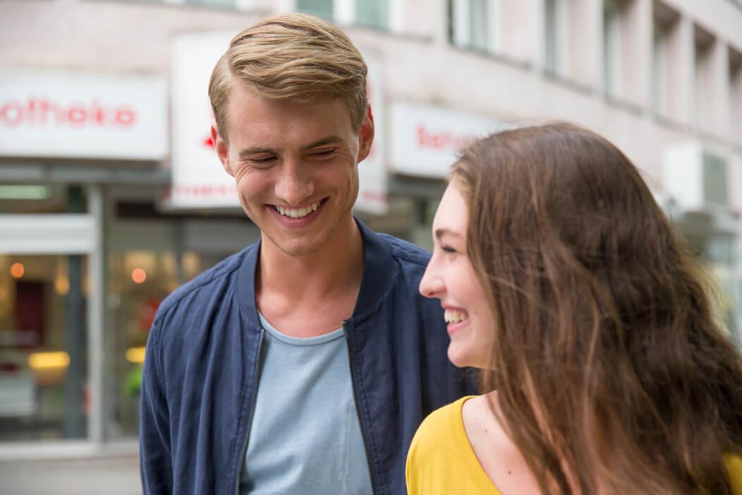 Junges, heterosexuelles Paar lacht sich gut gelaunt an.