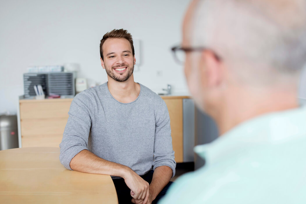 Young man smiling while talking to a professional counselor.