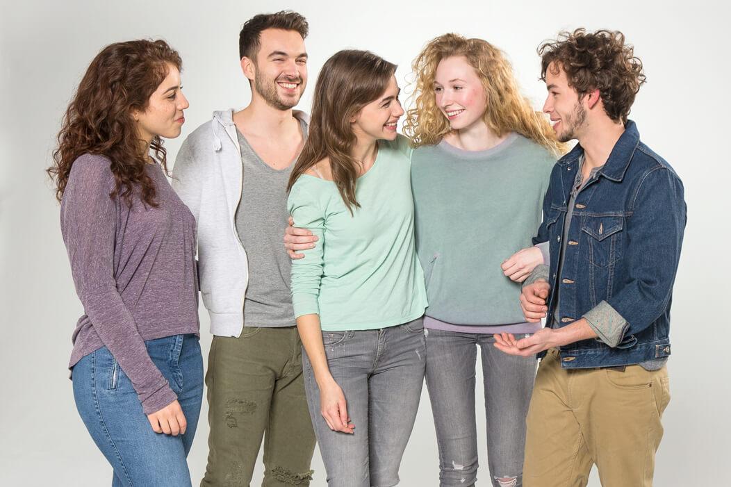 Eine gemische Gruppe steht Arm in Arm und lacht einander an.