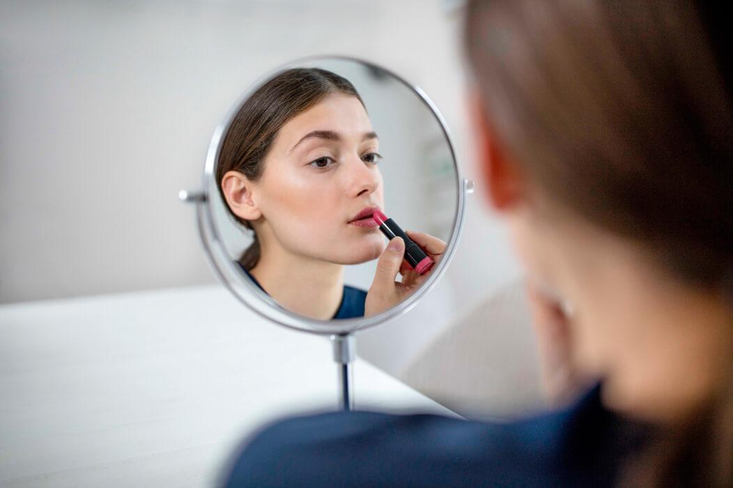 Trans* schaut in einen Spiegel und schminkt sich mit einem Lippenstift.