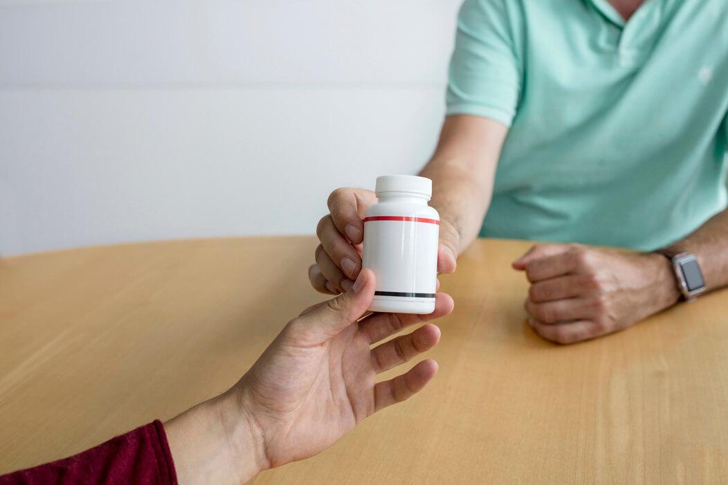Eine Medikamenten Packung wird einem Mann überreicht.