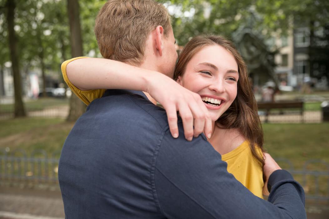 Junges, heterosexuelles Paar umarmt sich zur Begrüßung.