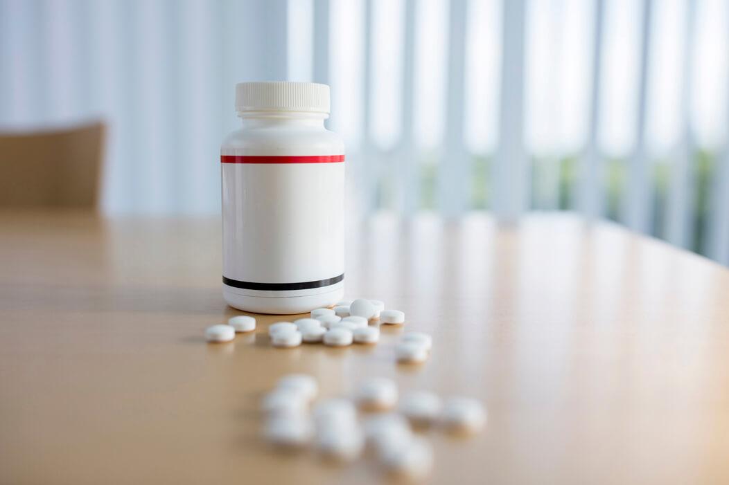 Eine Medikamentenpackung steht mit einzelnen Tabletten auf dem Tisch in einer Praxis.