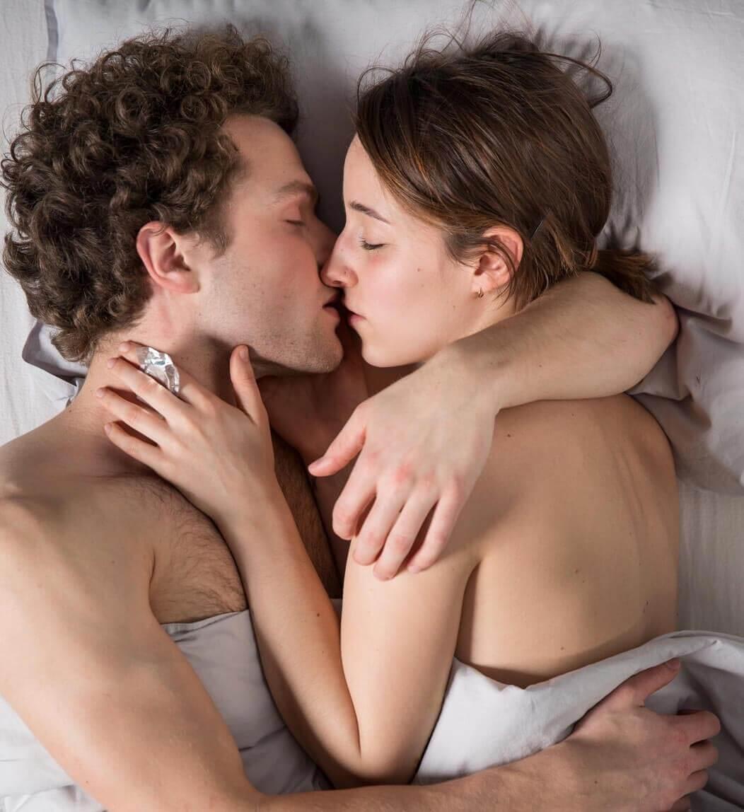 Heterosexuelles Paar umarmt und küsst sich unbekleidet unter der Bettdecke, die Frau hält ein Kondom