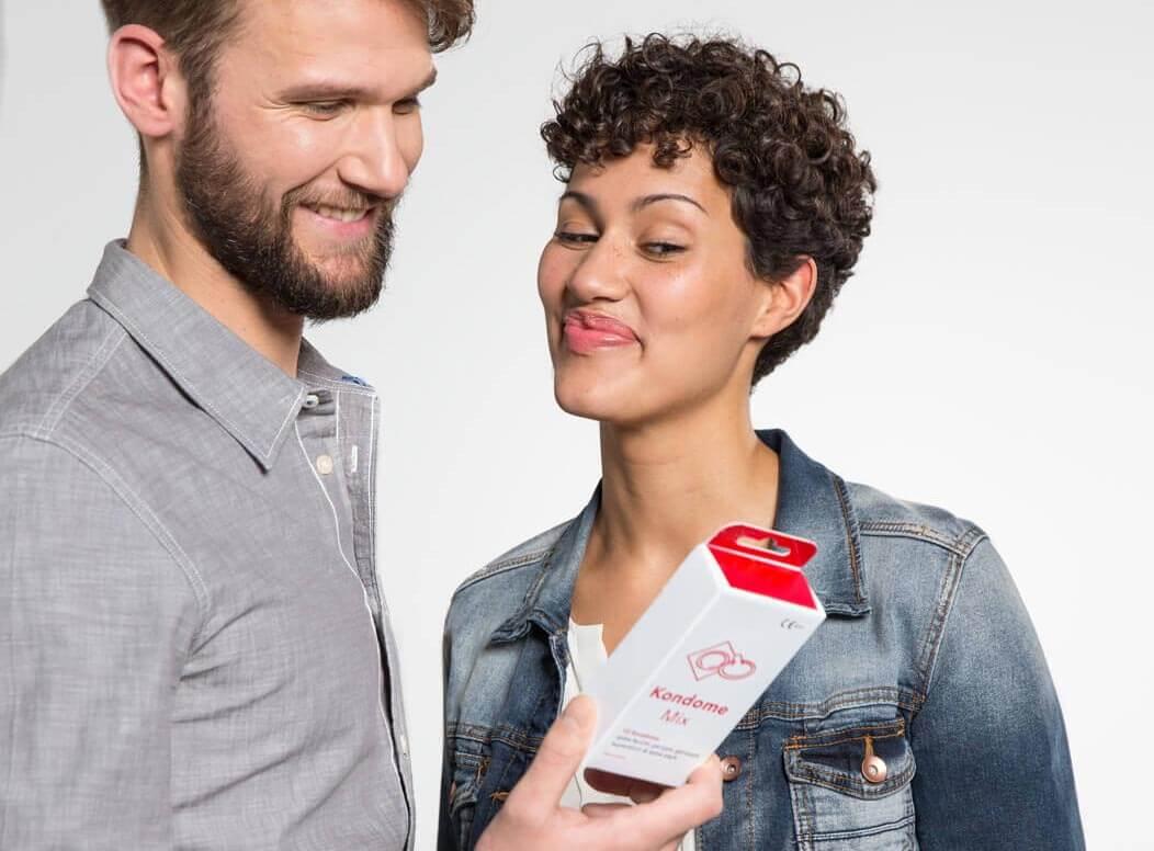 Heterosexuelles Paar schaut lächelnd und zwinkernd auf eine Packung Kondome.