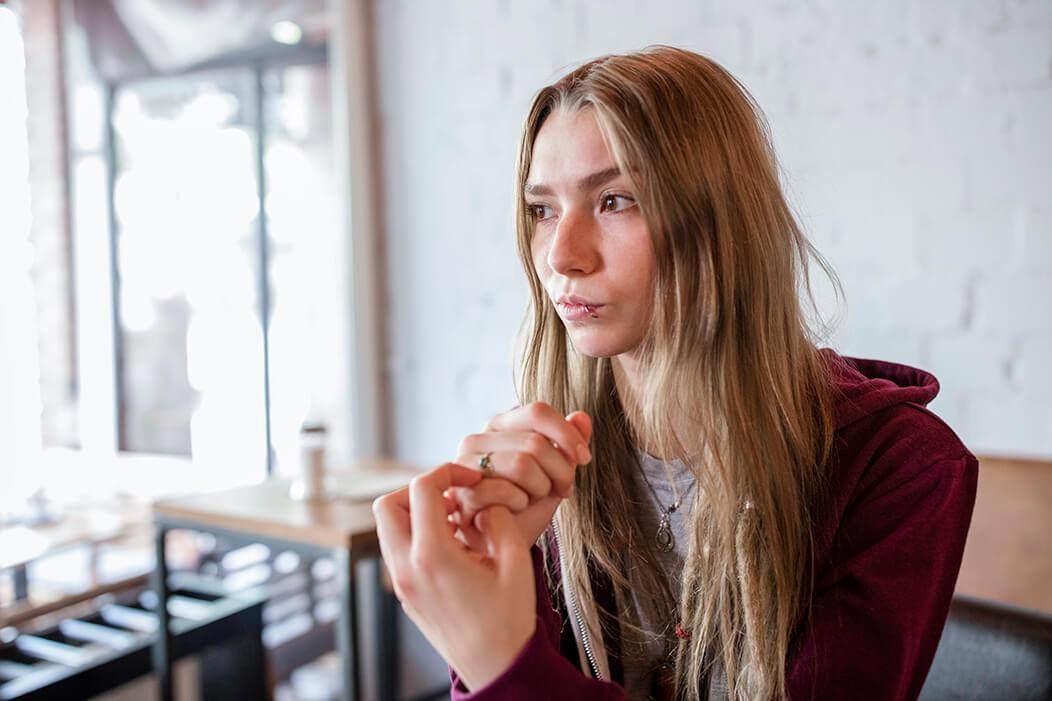 Junge Frau sitzt in einem Cafe und schaut nachdenklich.
