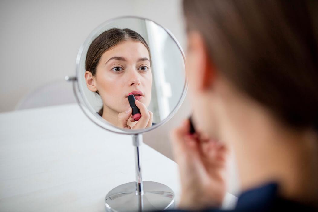 Ein *trans schaut in einen Spiegel und schminkt sich.
