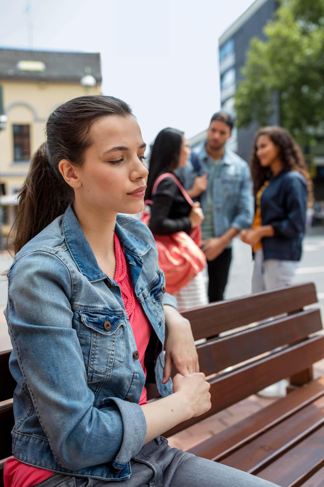 Frau sitzt abgegrenzt von einer Gruppe auf einer Parkbank.