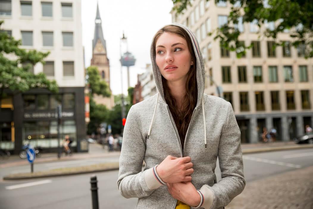 Junge Frau halt schützend ihren Kapuzenpullover zu und blickt aufgewühlt zur Seite.
