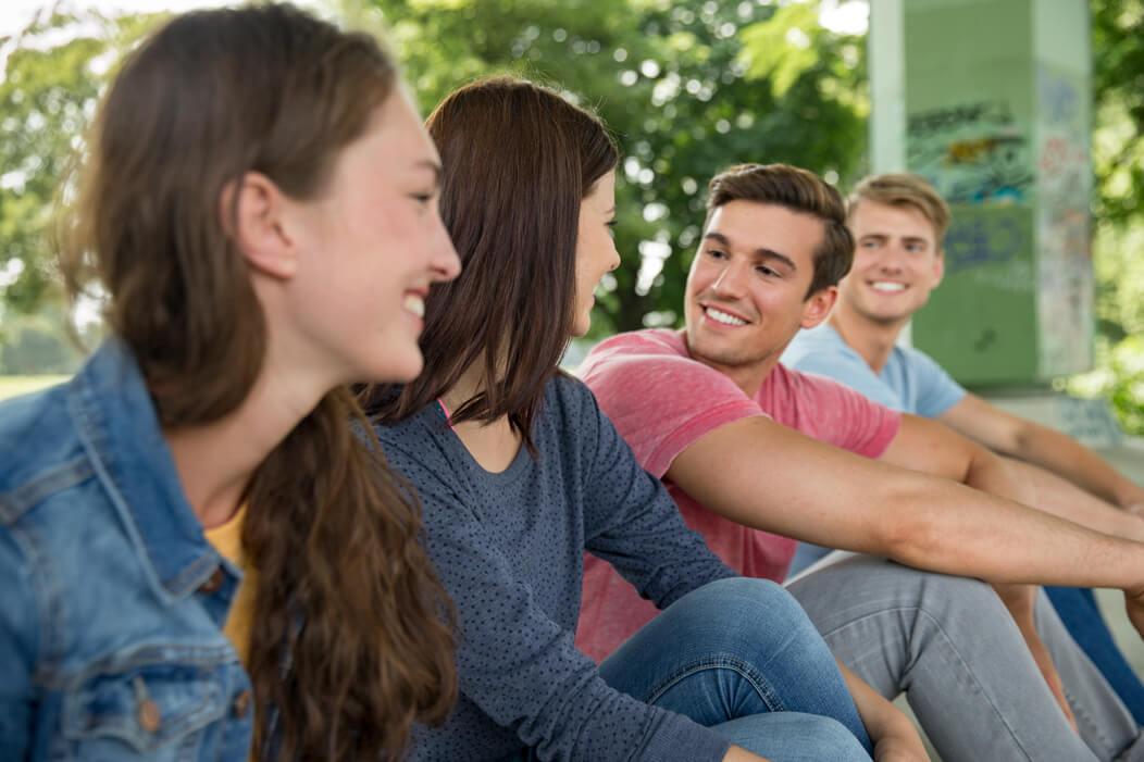 Eine gemische Gruppe junger Menschen sitzt gemeinsam gut gelaunt im Park.