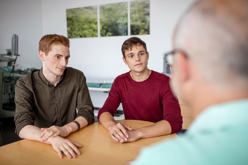 Schwules Paar sitzt in einer Praxis bei einem Gespräch.