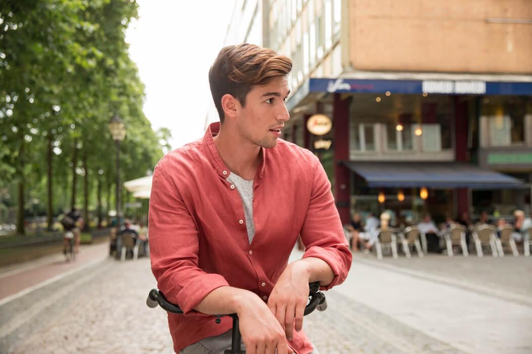Junger Mann sitzt auf Fahrrad und schaut sich mit entspanntem Gesichtsausdruck um.