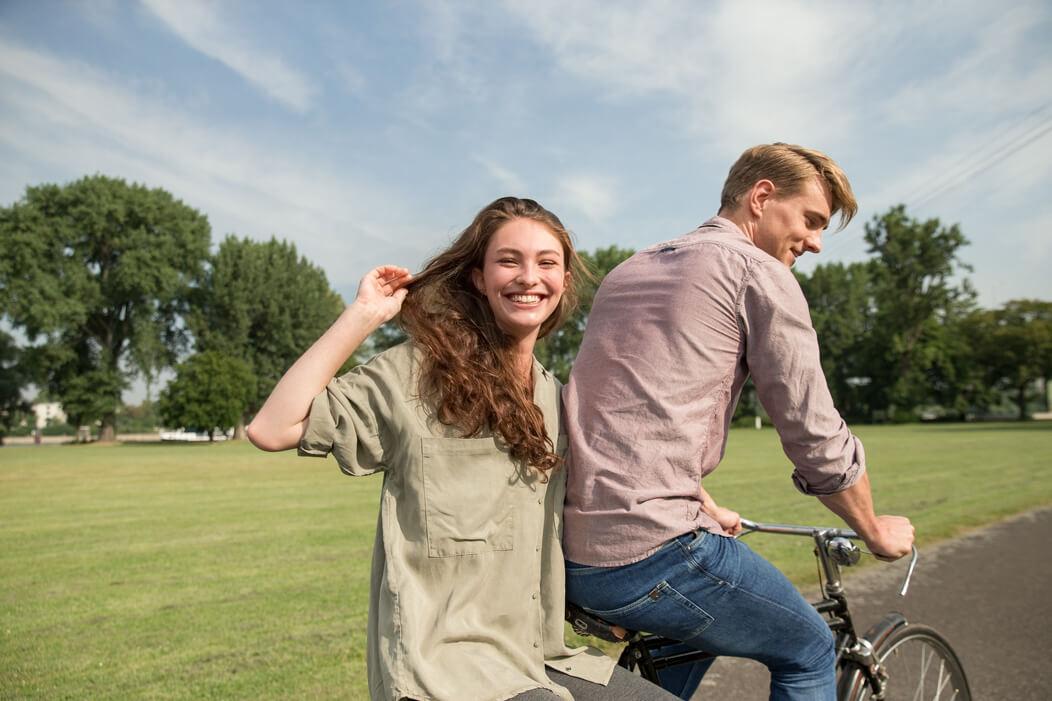 Junger Mann radelt mit seiner Partnerin auf dem Gepäckträger durch einen Park, beide lachen fröhlich.