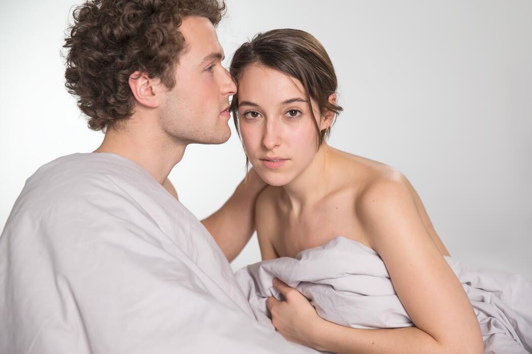 Heterosexuelles Paar unbekleidet unter einer Bettdecke mit ernstem, betroffenem Blick.