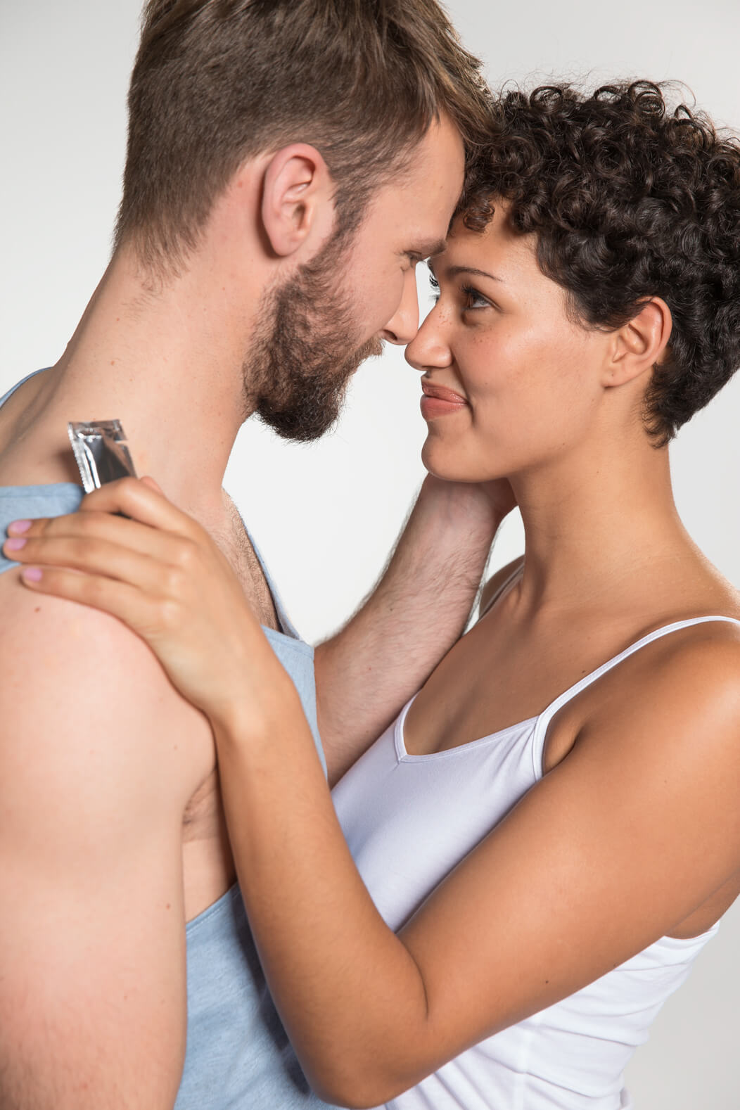 Heterosexuelles Paar in leichter Bekleidung umarmt sich. Die Frau hält ein verpacktes Kondom.