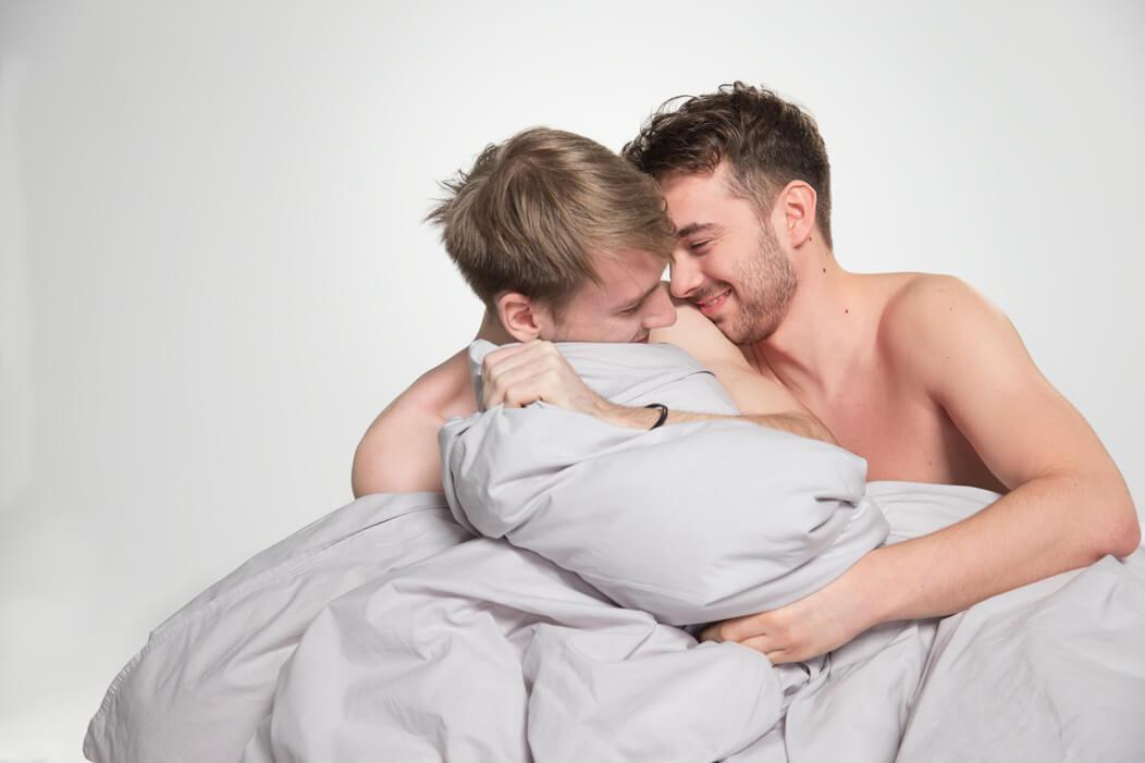 Schwules Paar kuschelt und albert unbekleidet unter der Bettdecke, beide lachen sich an.