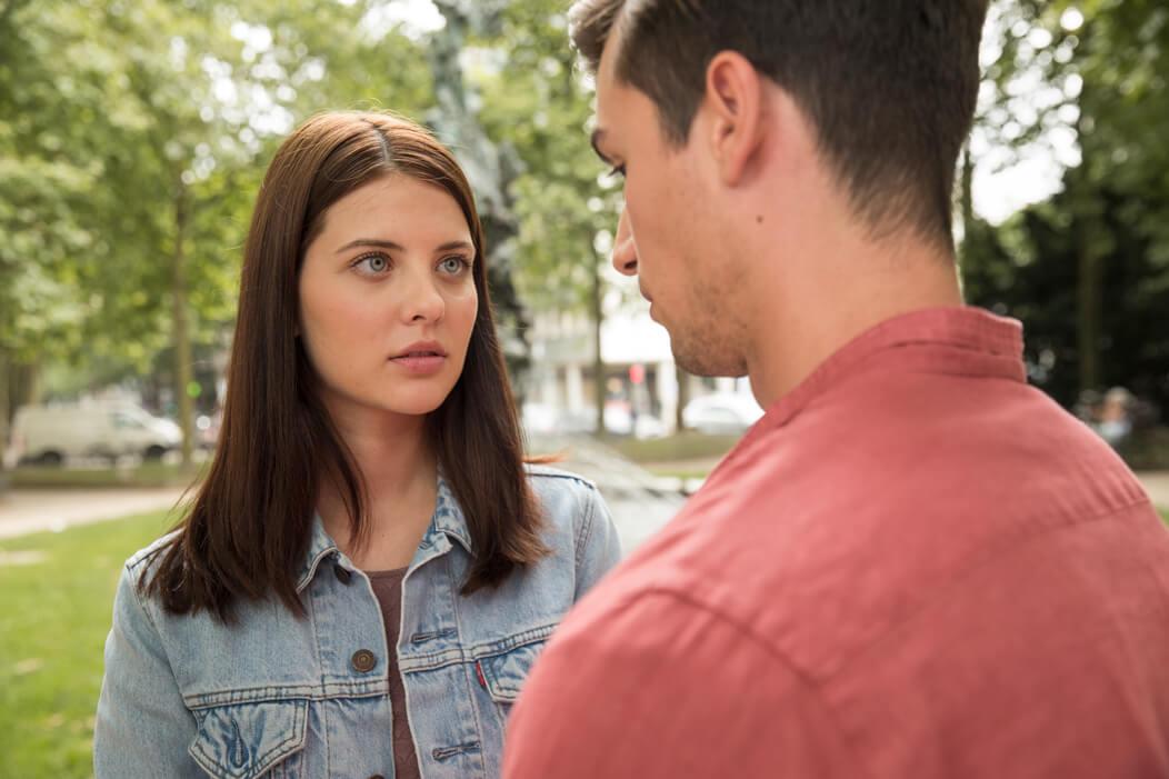 Junge Frau blickt ihren Partner im Gespräch erschrocken an.